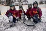 kids with can trophy and hockey sticks