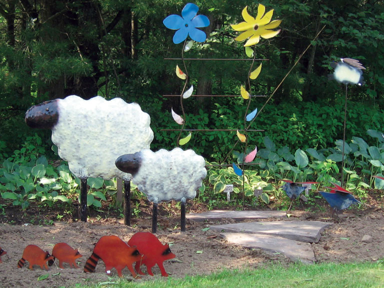 hand crafted sheep and flowers in garden
